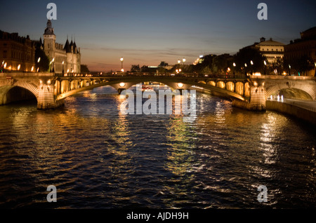 Pont au Change and the Conciergerie buildings left as seen from the Seine river after sunset - Stock Photo