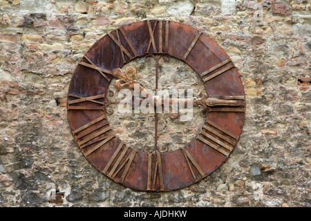 Old clock found on a stone wall in the courtyard of the Cathedral of the Assumption of Virgin Mary and St Stephen - Stock Photo