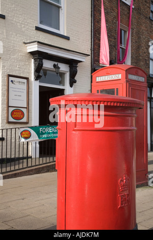 Red pillar box outside main Post Office in Bedale village North Yorkshire England UK - Stock Photo