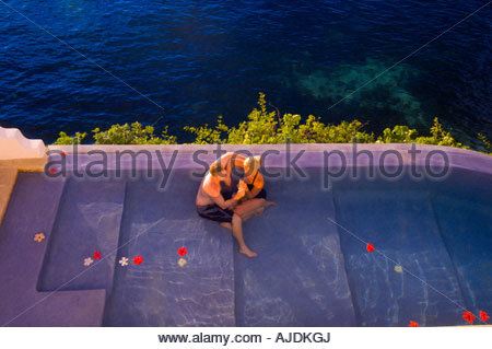 Couple relaxing in swimming pool by ocean - Stock Photo