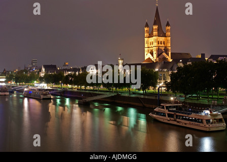 Cologne - Germany: St. Martin Church, the Rhine, and boats, by night. - Stock Photo