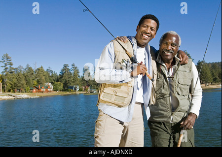 Senior man and son holding fishing rods by lake, smiling, (portrait) - Stock Photo