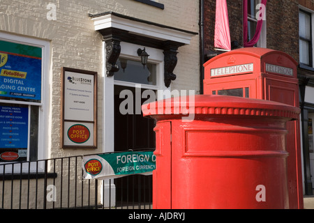 Red pillar box outside main Post Office in Bedale village centre North Yorkshire - Stock Photo