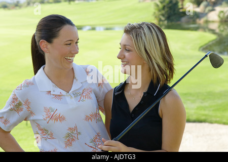 Two female golfers laughing to each other - Stock Photo
