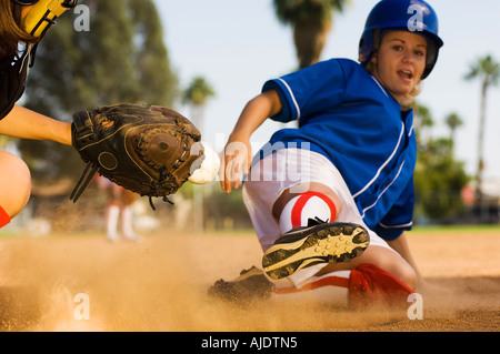 Softball player sliding into home plate - Stock Photo