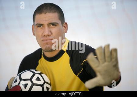 Goalkeeper holding ball, portrait - Stock Photo