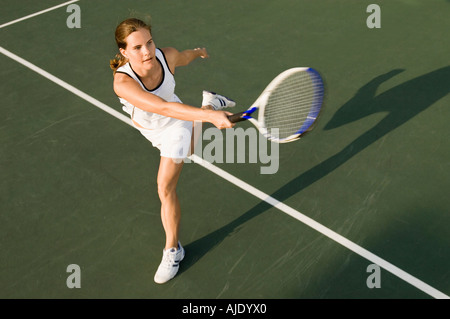 Tennis Player swinging racket in Forehand motion - Stock Photo