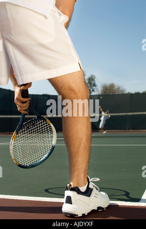 Tennis Player holding tennis racket, Waiting For Serve, low section, back view - Stock Photo
