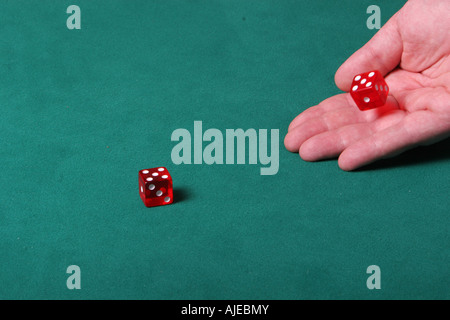 A hand throwing dices on a green felt table in a game of crabs - Stock Photo