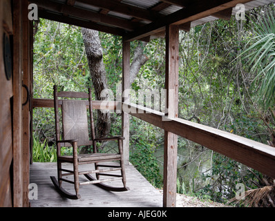 Rocking chair on porch of old farming house in Florida swamp - Stock Photo