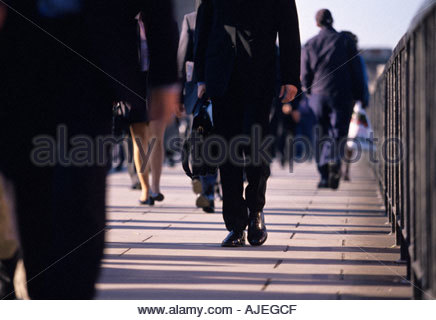 London Bridge: commuters crossing the bridge on the way to work in the morning - Stock Photo