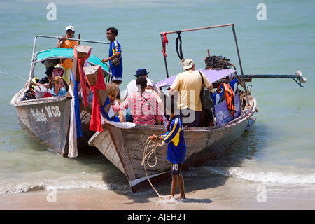 Visitors board long tail boats on Ao Nang Beach to get to other beaches and resorts Thailand - Stock Photo