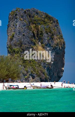Tall rock towers over white sand of popular Ko Poda island off Ao Nang beach Thailand