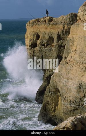 Man fishing on clifftop, Algar Seco, Algarve Portugal - Stock Photo