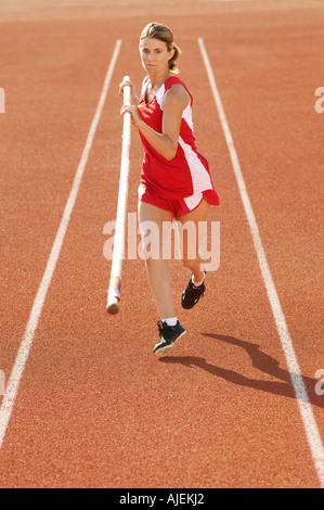 Athlete running with pole vault - Stock Photo