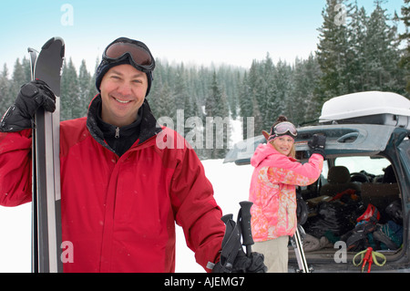 Couple standing in snow with skis, woman opening trunk of car. - Stock Photo