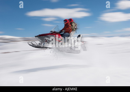 Couple jumping snowmobile in snow, mid air - Stock Photo