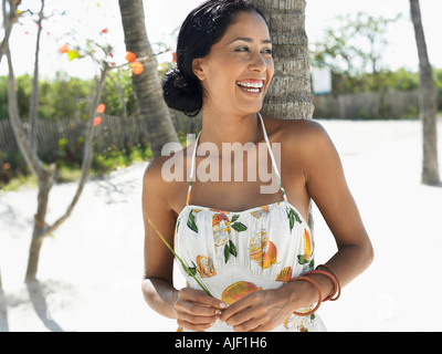 Woman leaning against palm tree on beach, half-length - Stock Photo