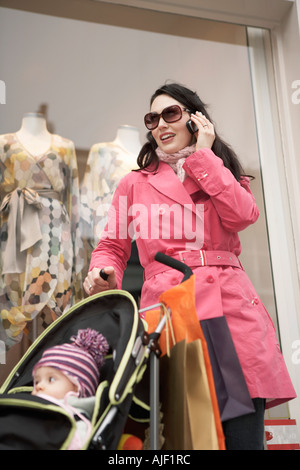 Mother with baby standing in front of shop using mobile phone - Stock Photo