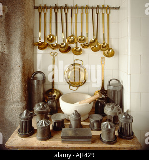 Various kitchen utensils including brass ladles and a pestle and mortar displayed on a wooden table at Saltram Devon - Stock Photo