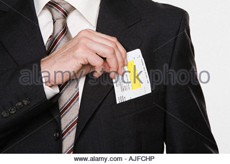 Businessman putting tickets in his pocket - Stock Photo