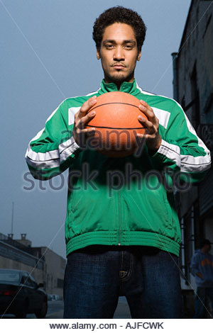Young man holding a basketball - Stock Photo