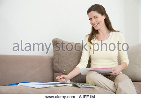 A woman working out bills - Stock Photo