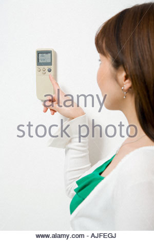 Woman pointing to thermostat - Stock Photo