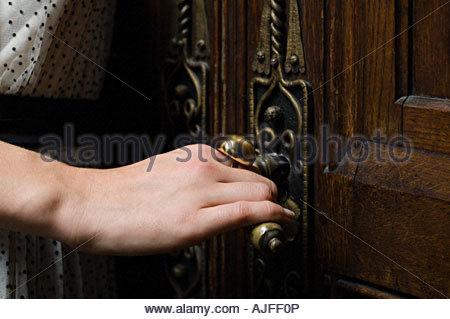 Woman opening a wooden door - Stock Photo
