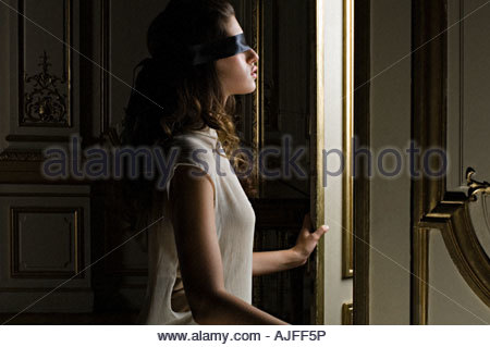 Blindfolded woman opening door - Stock Photo