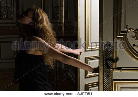 Woman walking through doors - Stock Photo