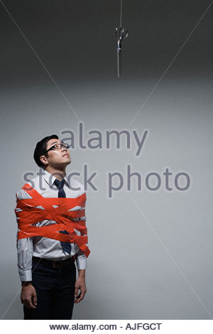 An office worker tied up in red tape - Stock Photo