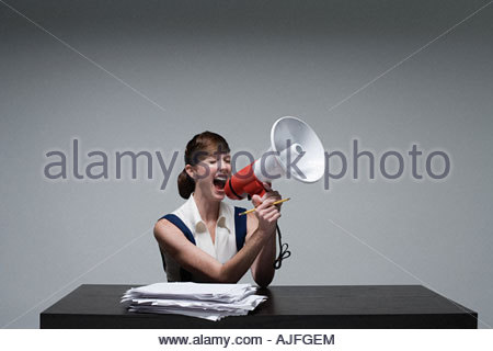 A businesswoman shouting on a loudspeaker - Stock Photo