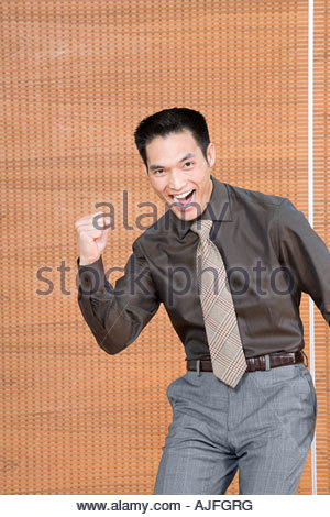 Portrait of excited asian young business man working on ...