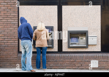 Thief looking over womans shoulder at cash machine - Stock Photo