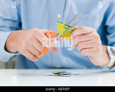 Man cutting up credit card - Stock Photo