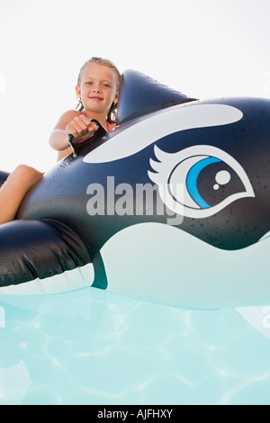Girl on inflatable whale - Stock Photo