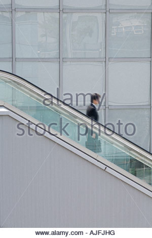 Man on an escalator - Stock Photo