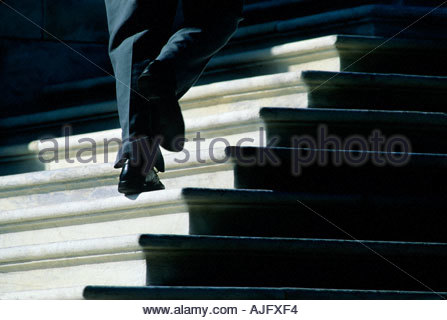 Man with black wingtip shoes running up white marble steps toward the United states Capitol building,  Washington - Stock Photo