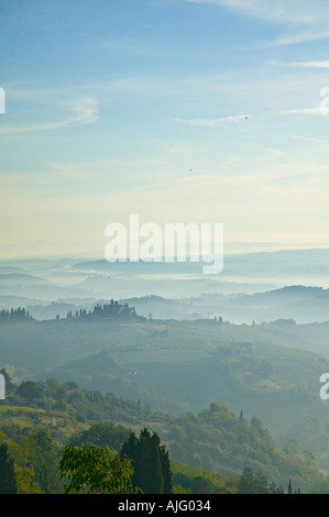 Misty view across the hills of Tuscany below a blue sky. Taken from San Gimignano, Tuscany, Italy - Stock Photo
