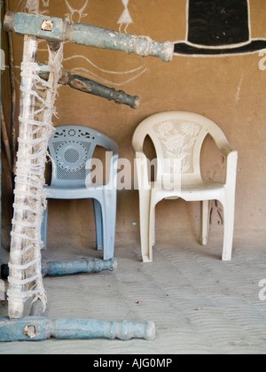 Plastic chairs contrast with handmade bed - Stock Photo