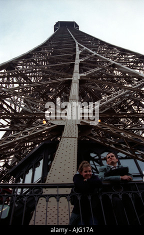 Wide angle view of the Eiffel Tower France with two tourists in the foreground - Stock Photo
