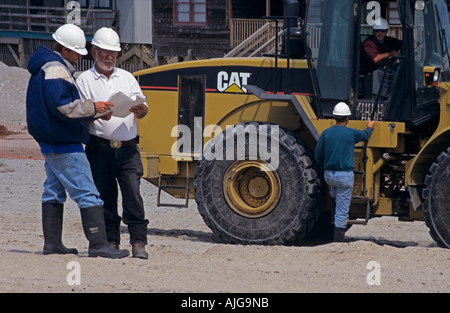 Surveyor and project manager on site with construction crew on building site USA - Stock Photo