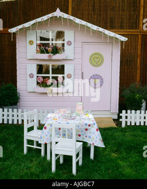 Children s wendy house in garden with table and chairs and tea party - Stock Photo