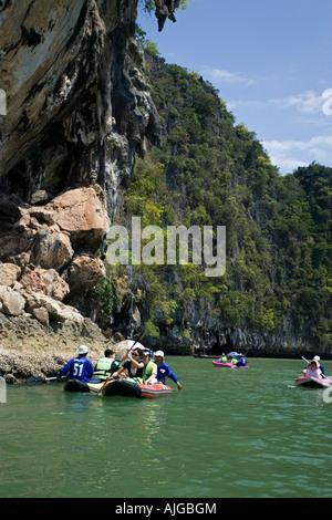 Visitors paddling in canoes Phang Nga Bay Thailand - Stock Photo