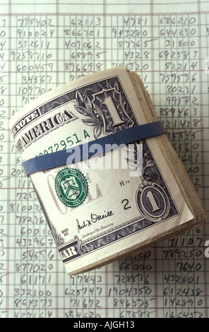 Cash roll of dollar bills on accounting records - Stock Photo
