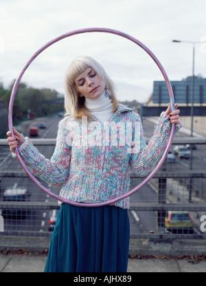 Woman holding hula hoop on motorway bridge - Stock Photo