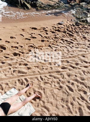 Woman sunbathing on sandy beach - Stock Photo