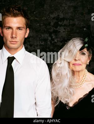 Young man and senior woman looking at camera - Stock Photo