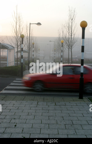 A speeding vehicle drives over a zebra crossing in a supermarket car park - Stock Photo